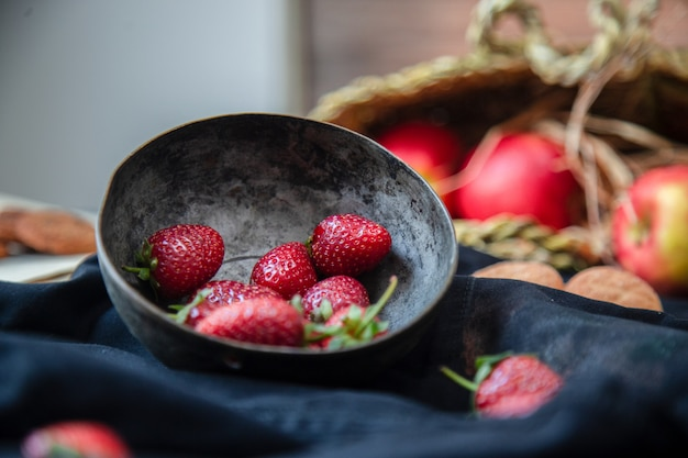 Strawberries inside bowl, cookies and apple basket on a black mat, blurred basket.