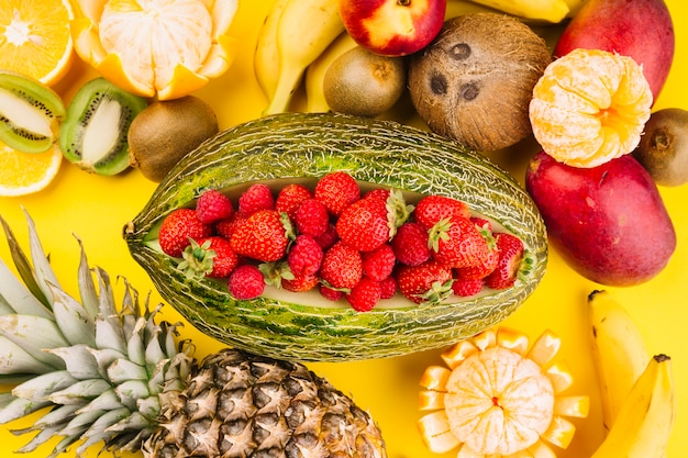 Strawberries inside the green netted melon with coconut; kiwi; mango; banana; pineapple and oranges on yellow background
