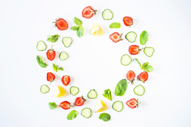 Strawberries, lemon, cucumber and mint are lined in the form of a wreath