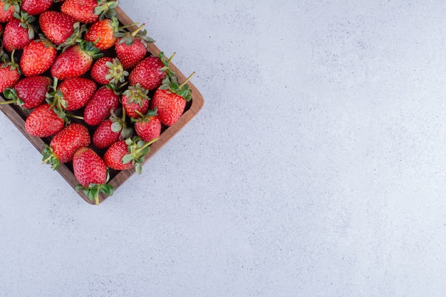 大理石の背景に小さなトレイにイチゴが並んでいます。高品質の写真