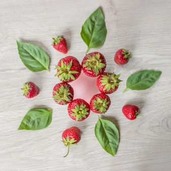 Strawberries lying on wooden table with leaves