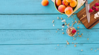 Strawberries; peach and oats on blue wooden plank