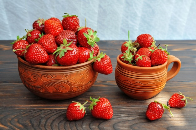 Strawberries in pottery on a wooden table. side view