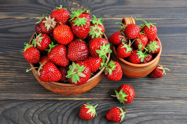 Strawberries in pottery on a wooden table. view from above