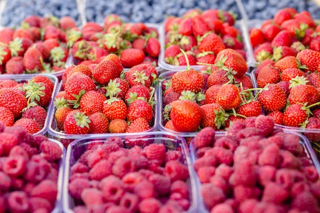 Strawberries, raspberries, blueberries in plastic transparent container box for sale on the grocery stand on the food market.