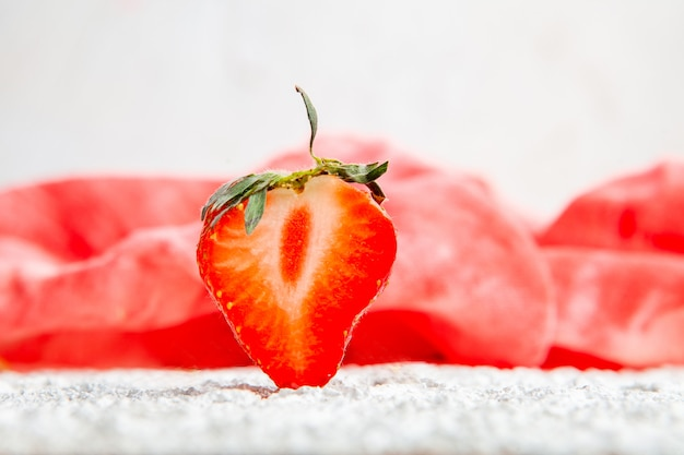 Strawberries on a red cloth and white textured background. side view.