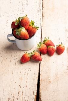 イチゴ、白いマグカップと古くて風化した木の板の上のいくつかの美しいイチゴ、選択的な焦点。