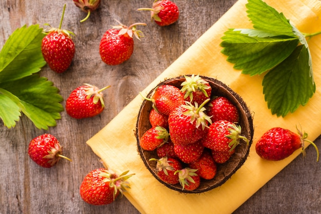 Strawberries in a small bowl on napkin on wooden table. top view