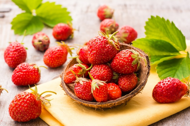 Strawberries in a small bowl on napkin on wooden table