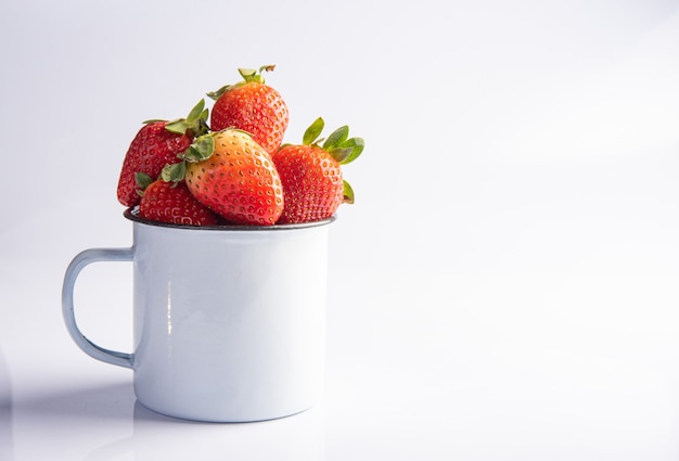 イチゴ、白い背景の上の白いマグカップのさまざまな美しいイチゴ、選択的な焦点
