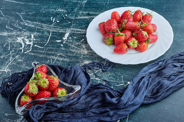 Strawberries in a white plate and inside glass cup.