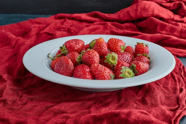 Strawberries in a white plate on red towel.