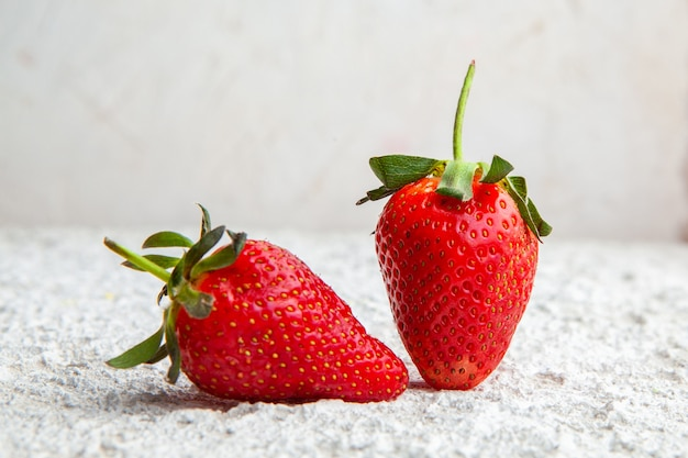 Strawberries on a white textured background. side view.