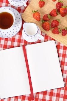 空のレシピ本とチェックテーブルクロス付きイチゴ