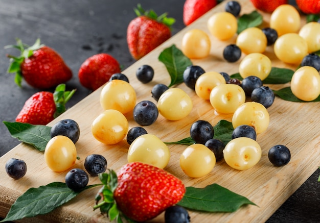Strawberries with blueberries, cherries, leaves high angle view on grey and cutting board
