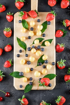 Strawberries with blueberries, cherries, leaves top view on grey and cutting board