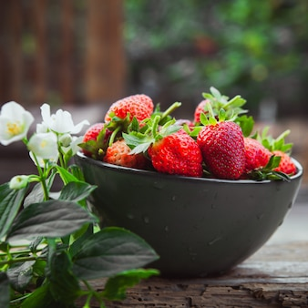 Strawberries with flowers on branch in a bowl on wooden and yard table, side view.