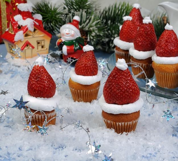 マフィンにクリスマスの帽子の形でホイップクリームとイチゴ