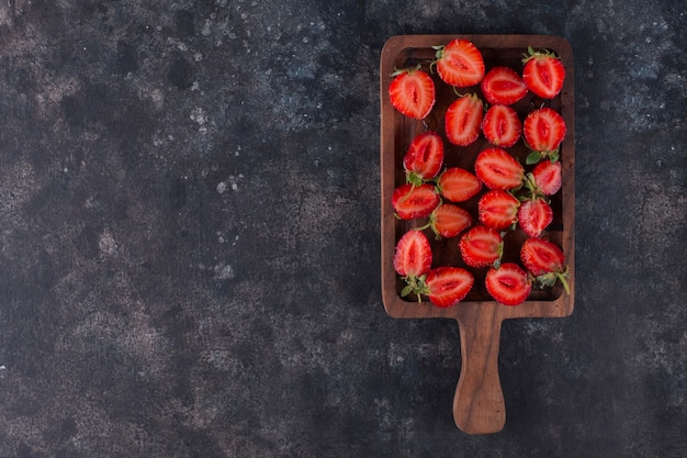 Strawberries on a wooden board on the grey marble, top view