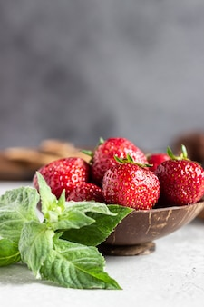 Strawberries in a wooden bowl with mint.