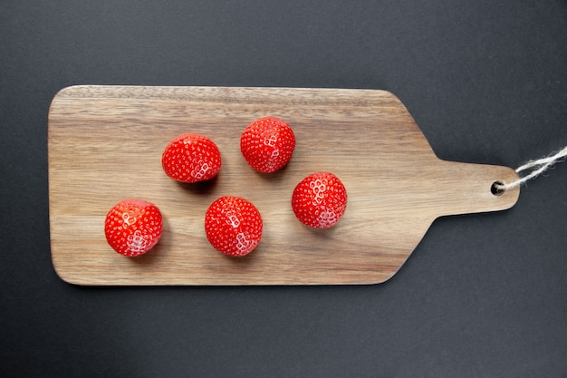 Strawberries on a wooden cutting board. black background. top view