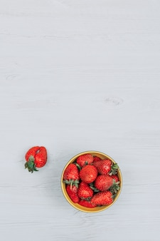 Strawberries in a yellow bowl with one strawberry flat lay on a white wooden background copy space for text