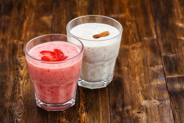 Strawberry and almond milk smoothies in a glass, wooden table