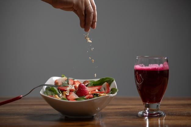 사탕무 주스와 귀리를 추가하는 손으로 딸기와 시금치 샐러드