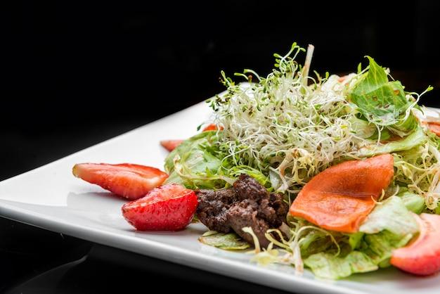 Салат из клубники, авокадо, салата с орехами кешью на тарелке