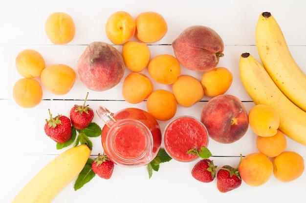 Клубничный банан пюре с мятой в стакан и кувшин на белом фоне деревянные. свежие фрукты бананы, персики и абрикосы фон