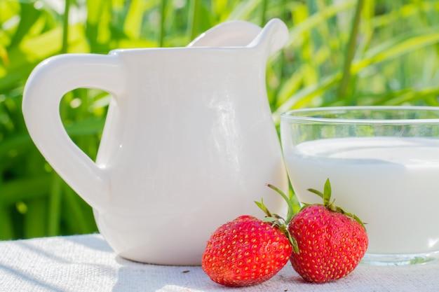 잔디의 배경에 대해 냅킨에 딸기 딸기, 용기 및 우유 컵