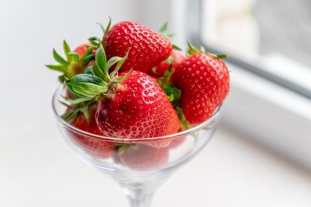 窓際の白い背景の上のガラスのゴブレットでイチゴの果実。夏のコンセプト