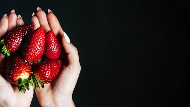 Strawberry berries in women 's hands.