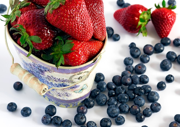 Strawberry and blueberry in colored bucket spilled
