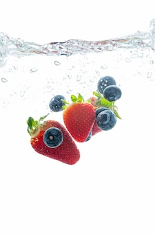 Strawberry and blueberry splashing into water, summer beverage concept