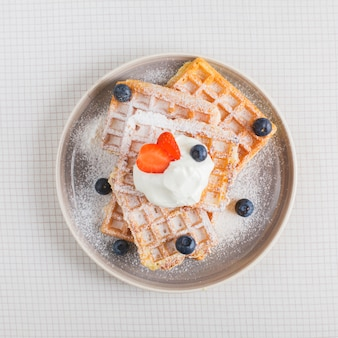 Strawberry and blueberry on whipped cream over the stack of waffles on plate over the checkered backdrop