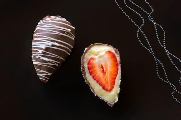 Клубничный конфет с шоколадом на черной поверхности