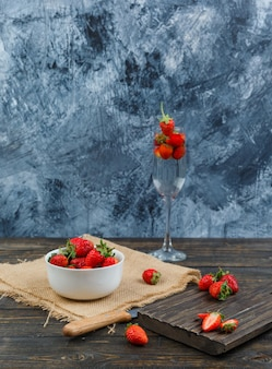 Strawberry in a bowl with wooden board