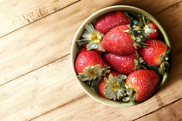 Strawberry in the bowl on a wooden