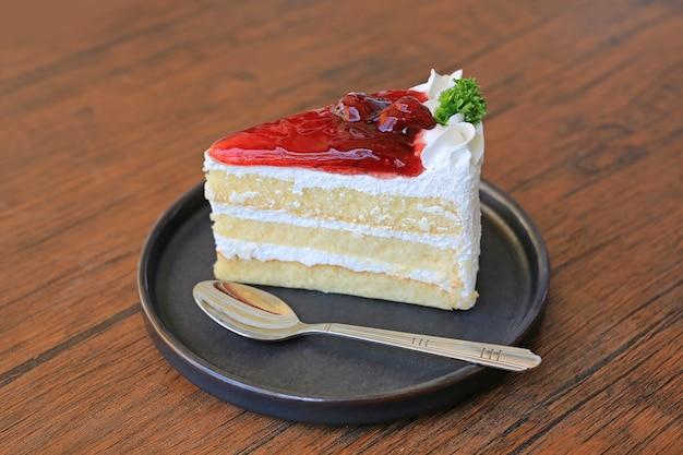 나무 테이블에 스푼으로 금속 쟁반에 딸기 케이크