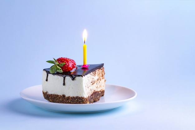 Strawberry cake with cream, dripping chocolate glaze and a lit candle in a plate