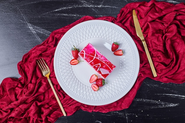 Strawberry cake with golden cutlery on white plate.