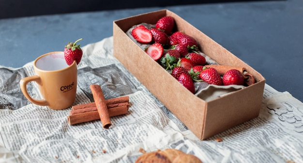 Strawberry carton box with cup and cinnamons on a newspaper.