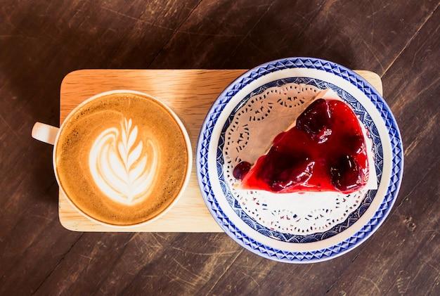 テーブル上のストロベリーチーズケーキとラテコーヒー