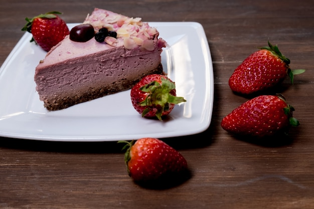 Strawberry cheesecake on black plate over rustic wooden background. top view.