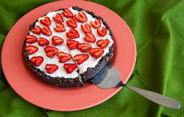 ハート型のイチゴで飾られたイチゴのチーズケーキは、サンゴ色のプレートの上にあり、緑のナプキンの上に立って、スライスを切り取りました。