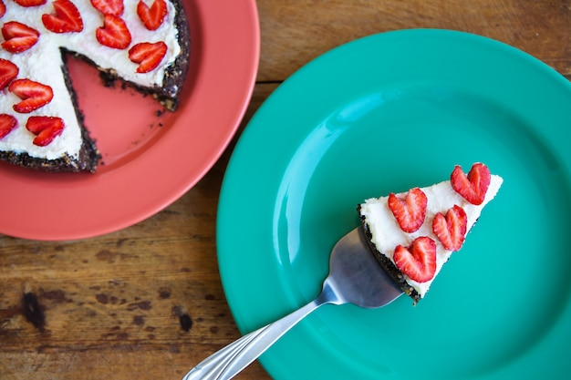 Strawberry cheesecake decorated with heart-shaped strawberries lies on a plate and stands on a wooden table, cut off a slice.