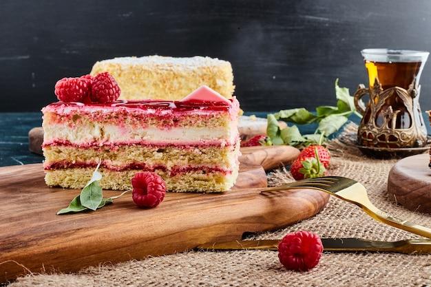 나무 보드에 티 한 잔과 딸기 치즈 케이크.