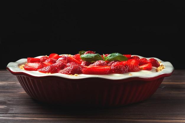 나무 테이블에 빨간색 세라믹 베이킹 접시에 바질 잎 딸기 치즈 케이크