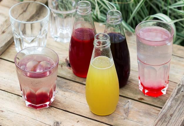 イチゴ、チェリー、ルバーブのシロップと庭の木製テーブルの上の水でグラス。
